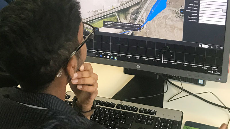 Young student creating digital road design using Bentley System Software